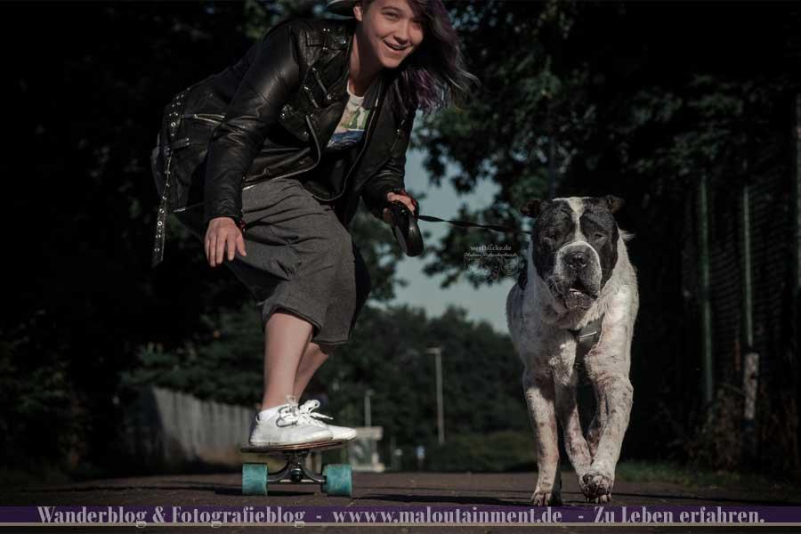 Frau fährt Longboard mit Hund